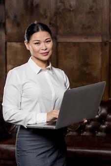 Donna di affari dell'angolo alto con il computer portatile