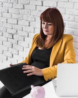 Donna di affari dell'angolo alto concentrata su lavoro
