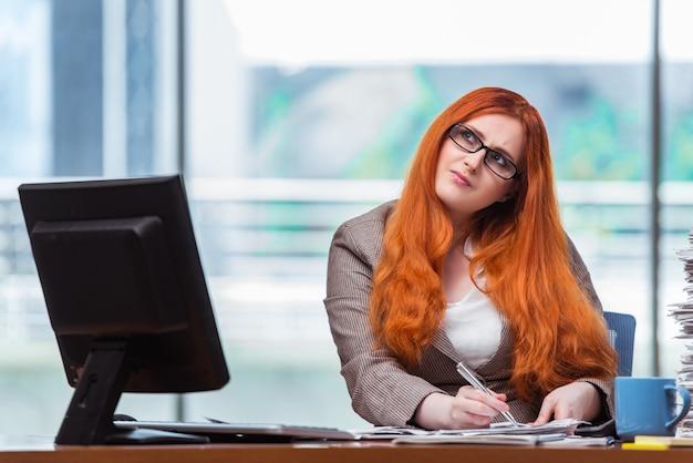 Donna di affari della testarossa che si siede al suo scrittorio nell'ufficio