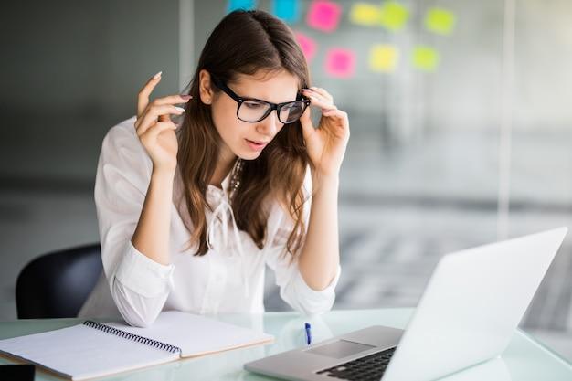 Donna di affari delusa che lavora al computer portatile nel suo ufficio vestita in abiti bianchi