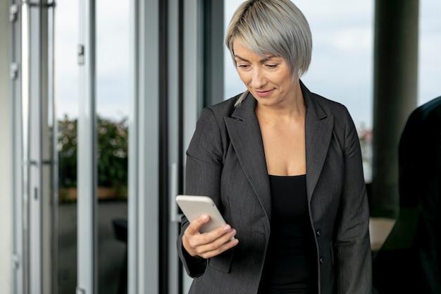 Donna di affari di angolo basso che esamina telefono