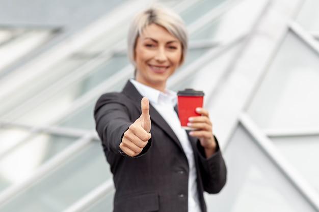 Donna di affari di angolo basso che mostra segno giusto