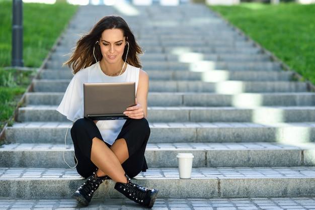 Donna di affari di mezza età che lavora con il suo computer portatile che si siede sul pavimento