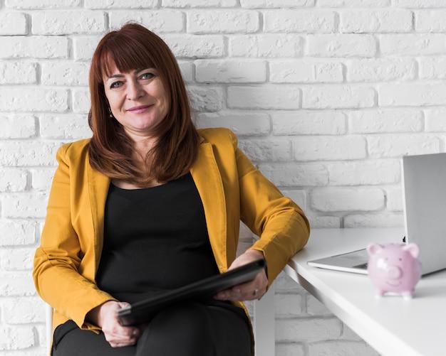 Donna di affari di smiley dell'angolo alto sul lavoro