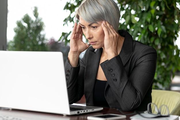 Donna di affari di vista frontale che esamina computer portatile