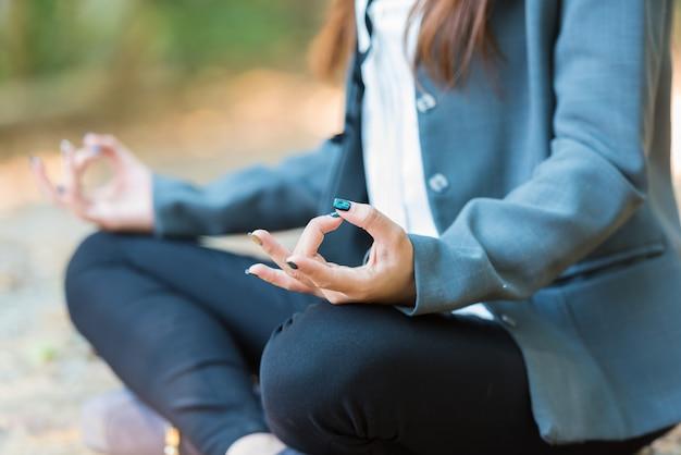 Donna di affari di yoga che fa meditazione con lo spiritual nel parco.