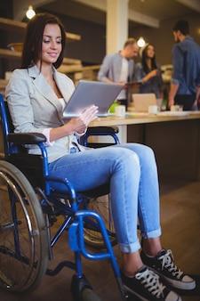 Donna di affari disabile che sorride mentre per mezzo della compressa digitale