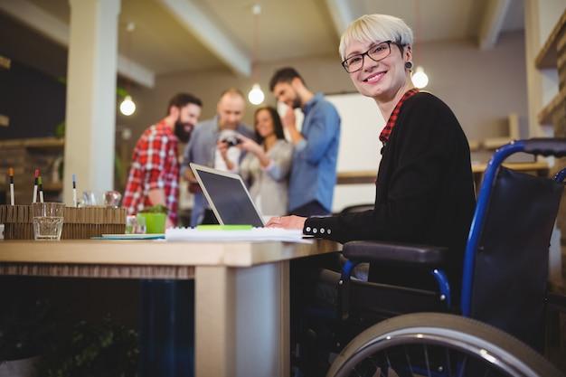 Donna di affari disabile felice che per mezzo del computer portatile allo scrittorio