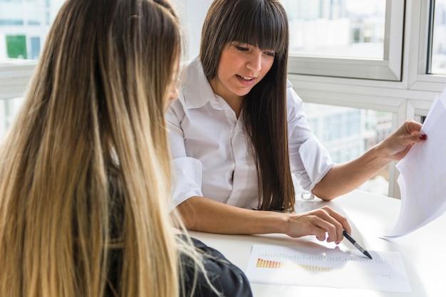 Donna di affari due che analizza il rapporto di affari nell'ufficio