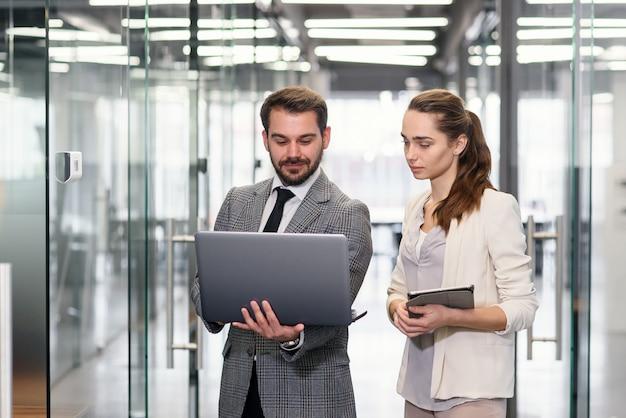 Donna di affari ed uomo d'affari nel computer portatile che sta e che discute progetto nelle finestre vuote dell'ufficio con la vista della città.