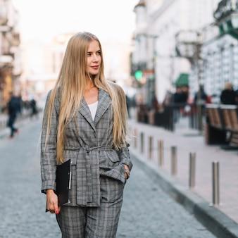 Donna di affari elegante che cammina in città con appunti