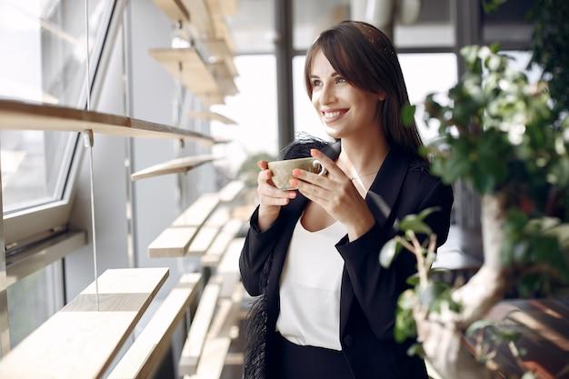 Donna di affari elegante che lavora in un ufficio e che beve un caffè