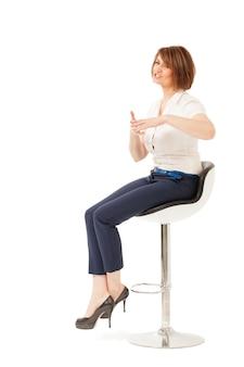 Donna di affari elegante che parla mentre sedendosi sulla sedia