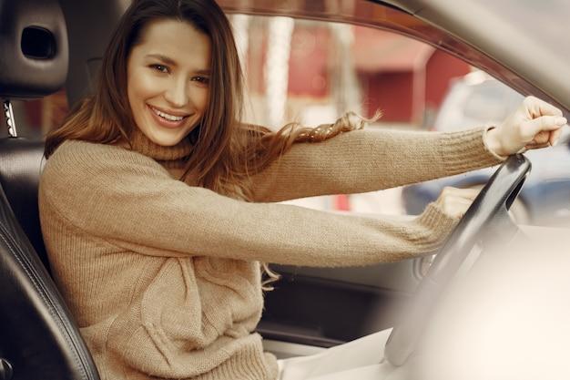 Donna di affari elegante che si siede in un'automobile