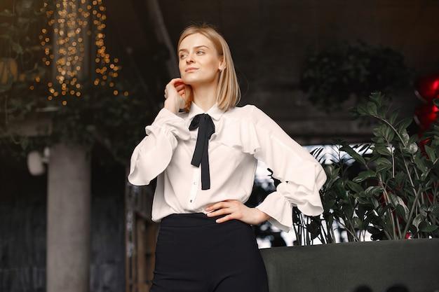Donna di affari elegante che sta nell'ufficio
