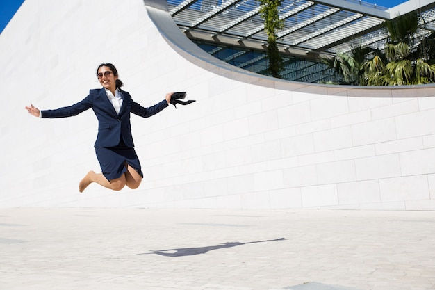 Donna di affari emozionante allegra che celebra successo