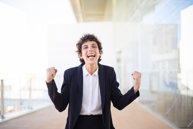 Donna di affari emozionante che agita i pugni