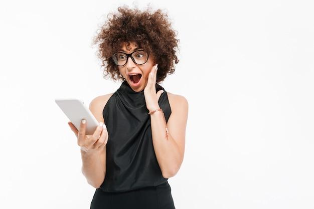 Donna di affari emozionante felice in occhiali che esaminano il computer della compressa