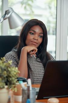 Donna di affari etnica adulta al tavolo di lavoro
