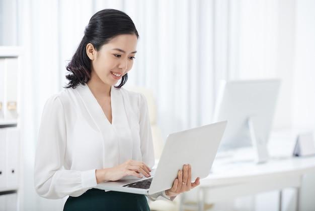 Donna di affari etnica affascinante che per mezzo del computer portatile