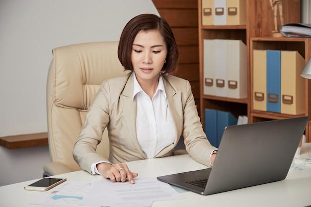 Donna di affari etnica che lavora con la carta