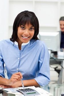 Donna di affari etnica che per mezzo di un calcolatore