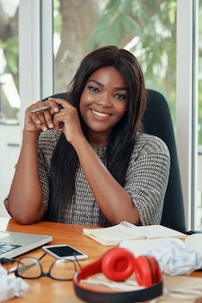Donna di affari etnica contenta allo scrittorio funzionante