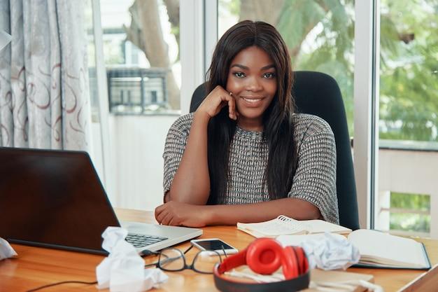 Donna di affari etnica sorridente al tavolo di lavoro