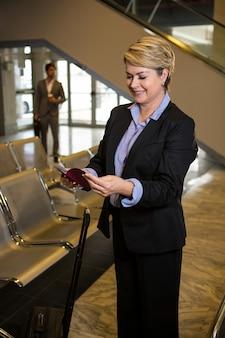 Donna di affari felice che esamina il suo passaporto mentre stando