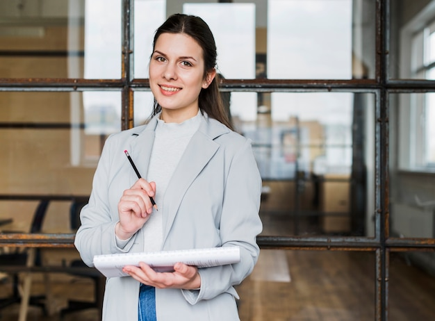 Donna di affari felice che esamina macchina fotografica con la matita e il diario della tenuta