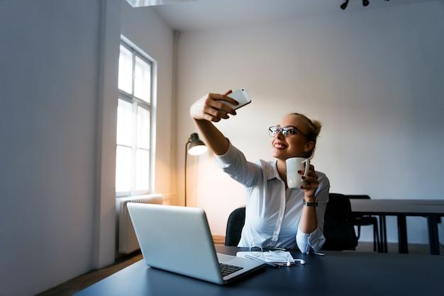 Donna di affari felice che fa selfie in ufficio con la tazza di caffè