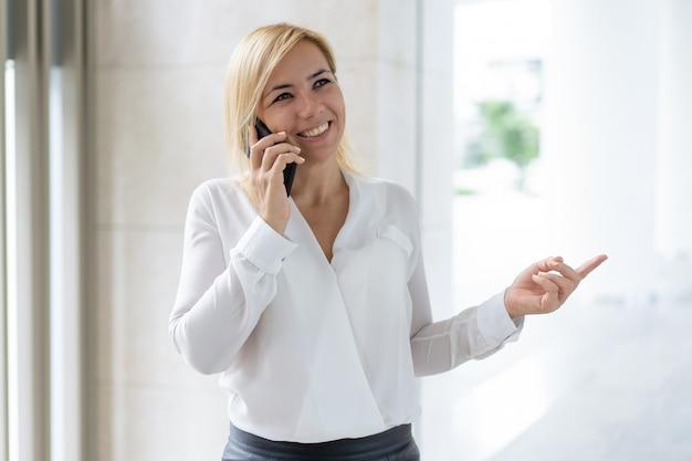 Donna di affari felice che ha conversazione piacevole del telefono