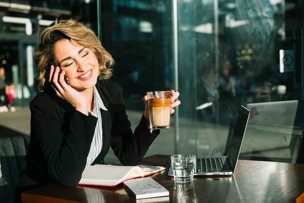 Donna di affari felice che parla sullo smartphone mentre tenendo vetro del frappè del cioccolato in ristorante
