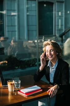 Donna di affari felice che si siede nel ristorante facendo uso del telefono cellulare