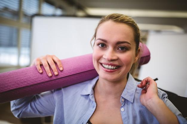 Donna di affari felice con la borsa e la stuoia di esercizio