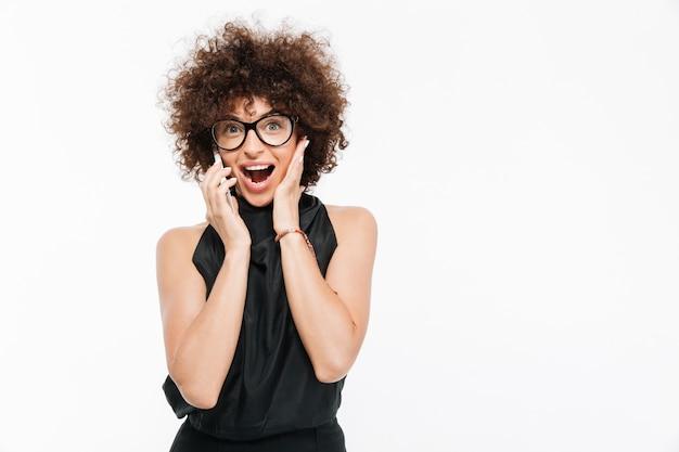 Donna di affari felice emozionante in occhiali che parla sul telefono cellulare