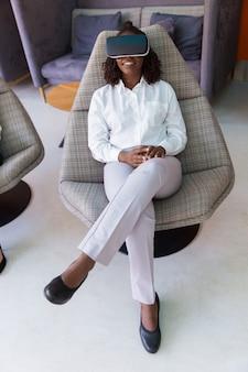 Donna di affari felice positiva che gode dell'esperienza di vr