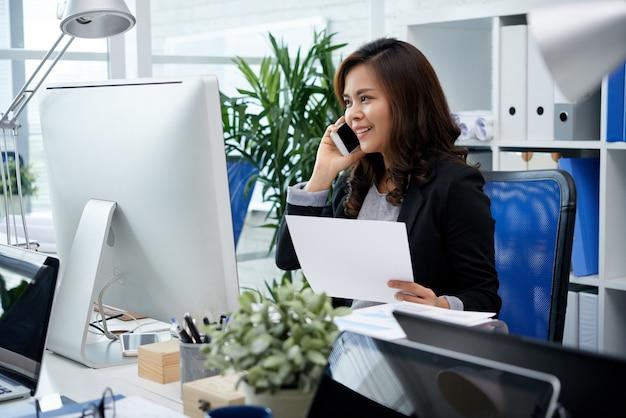 Donna di affari filippina sorridente che si siede allo scrittorio in ufficio e che parla sul telefono cellulare