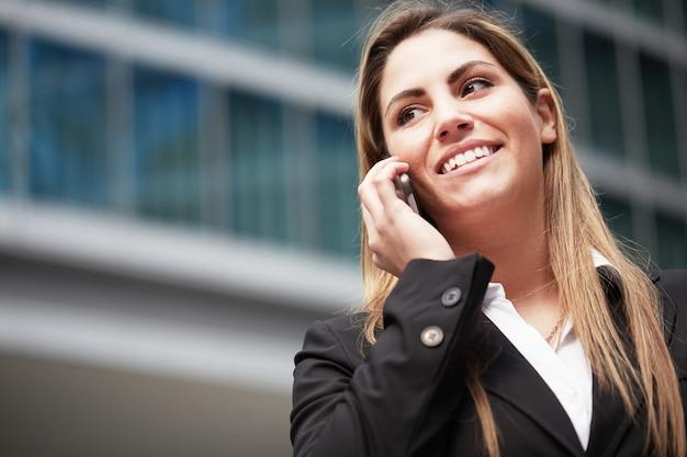 Donna di affari graziosa che parla con cellulare nell'ambiente urbano