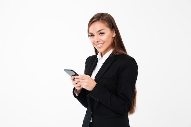 Donna di affari graziosa felice che chiacchiera dal telefono.