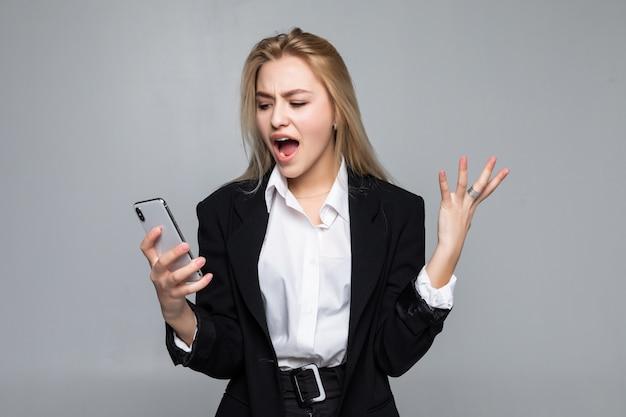 Donna di affari graziosa sorpresa che chiacchiera dalla condizione del telefono isolata.