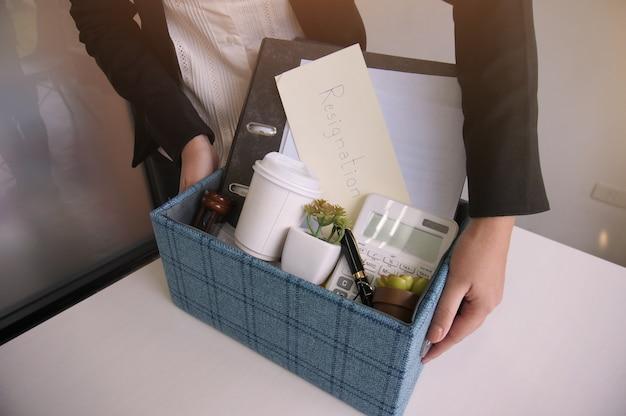 Donna di affari holding stuff resign depressare o trasportare scatola di cartone da scrivania in ufficio