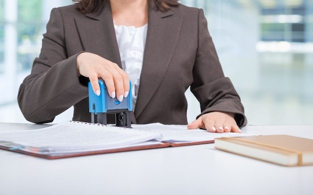 Donna di affari, impiegato che mette bollo sui documenti, contratto, facendo un affare, concetto di affari