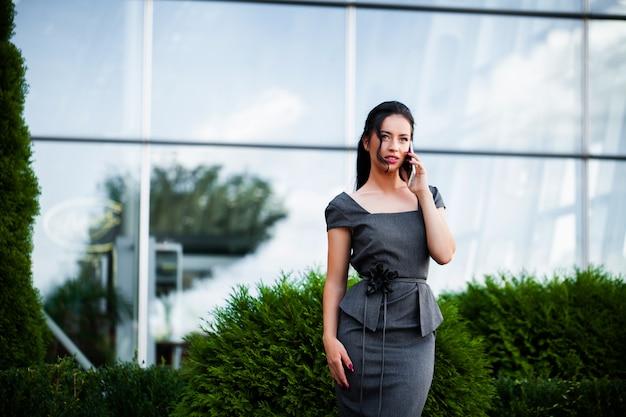 Donna di affari in aeroporto che parla sullo smartphone mentre camminando con il bagaglio a mano in aeroporto che va al cancello