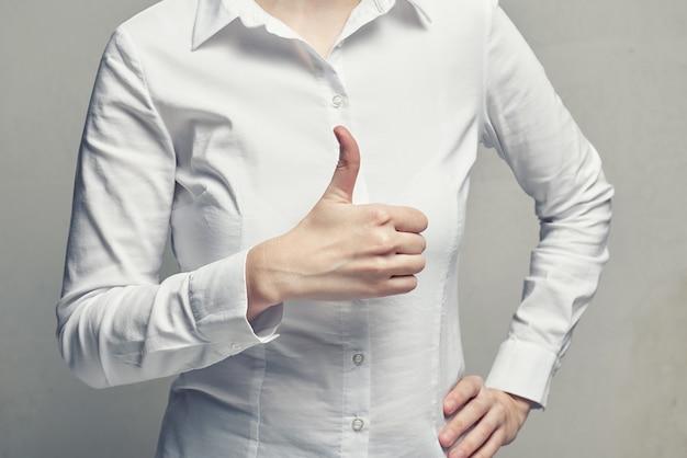 Donna di affari in camicetta che mostra il pollice di gesto in su