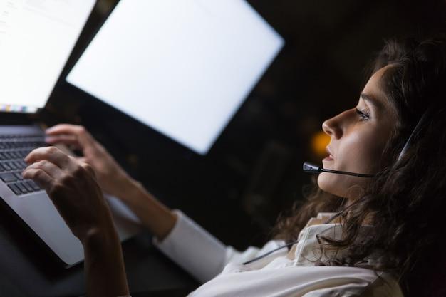 Donna di affari in cuffia avricolare che per mezzo del computer portatile