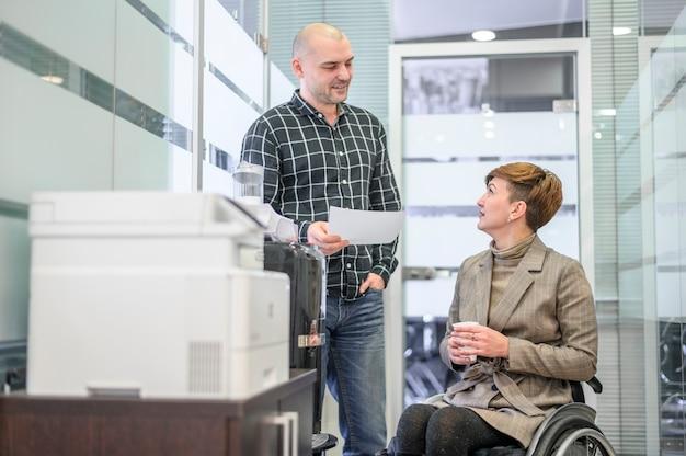 Donna di affari in sedia a rotelle in ufficio