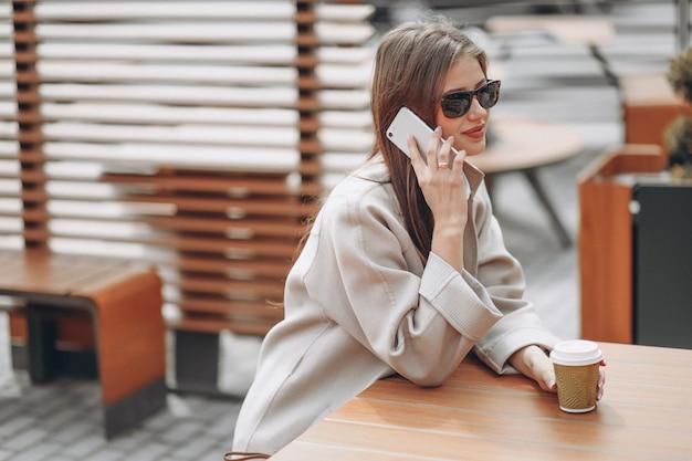 Donna di affari in un caffè che beve caffè, usando il telefono