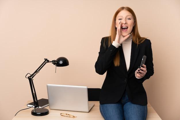 Donna di affari in un ufficio che grida con la bocca spalancata