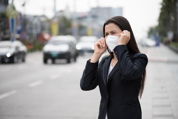 Donna di affari in un vestito che indossa maschera protettiva e tosse